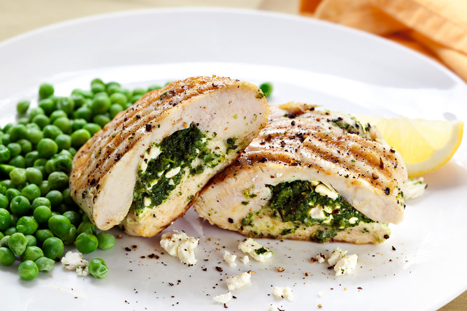 A plate of chicken stuffed with cheese and spinach and a side of peas.