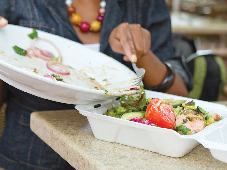 Una persona usa un tenedor para mover la comida de un plato a un recipiente para llevar.