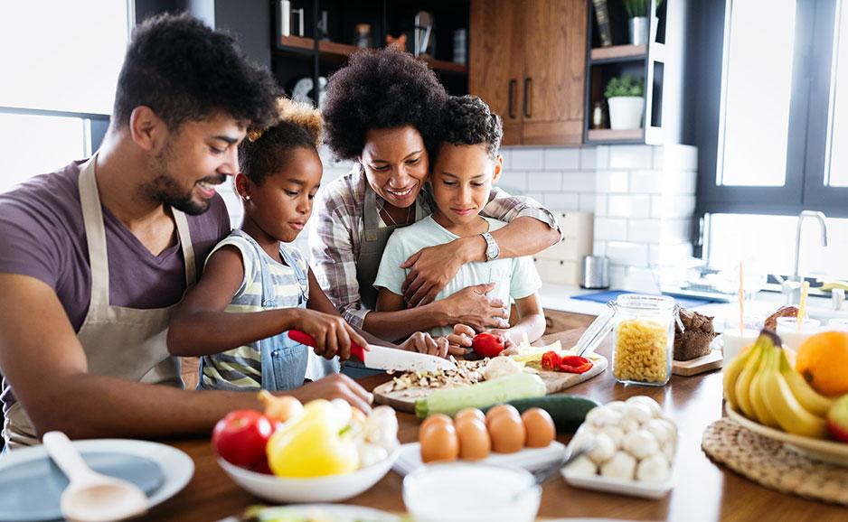 Familia feliz en la cocina, divirtiéndose mientras cocinan un plato saludable juntos.