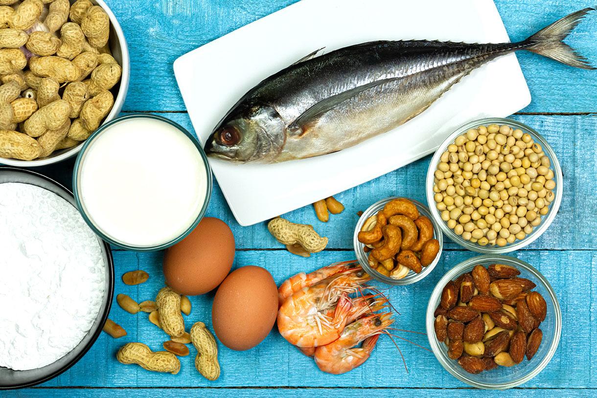 Los principales alérgenos de los alimentos son la leche, los huevos, el maní, el pescado, los mariscos, el trigo, la soja y los frutos secos - mesa de madera rústica azul, vista desde arriba.