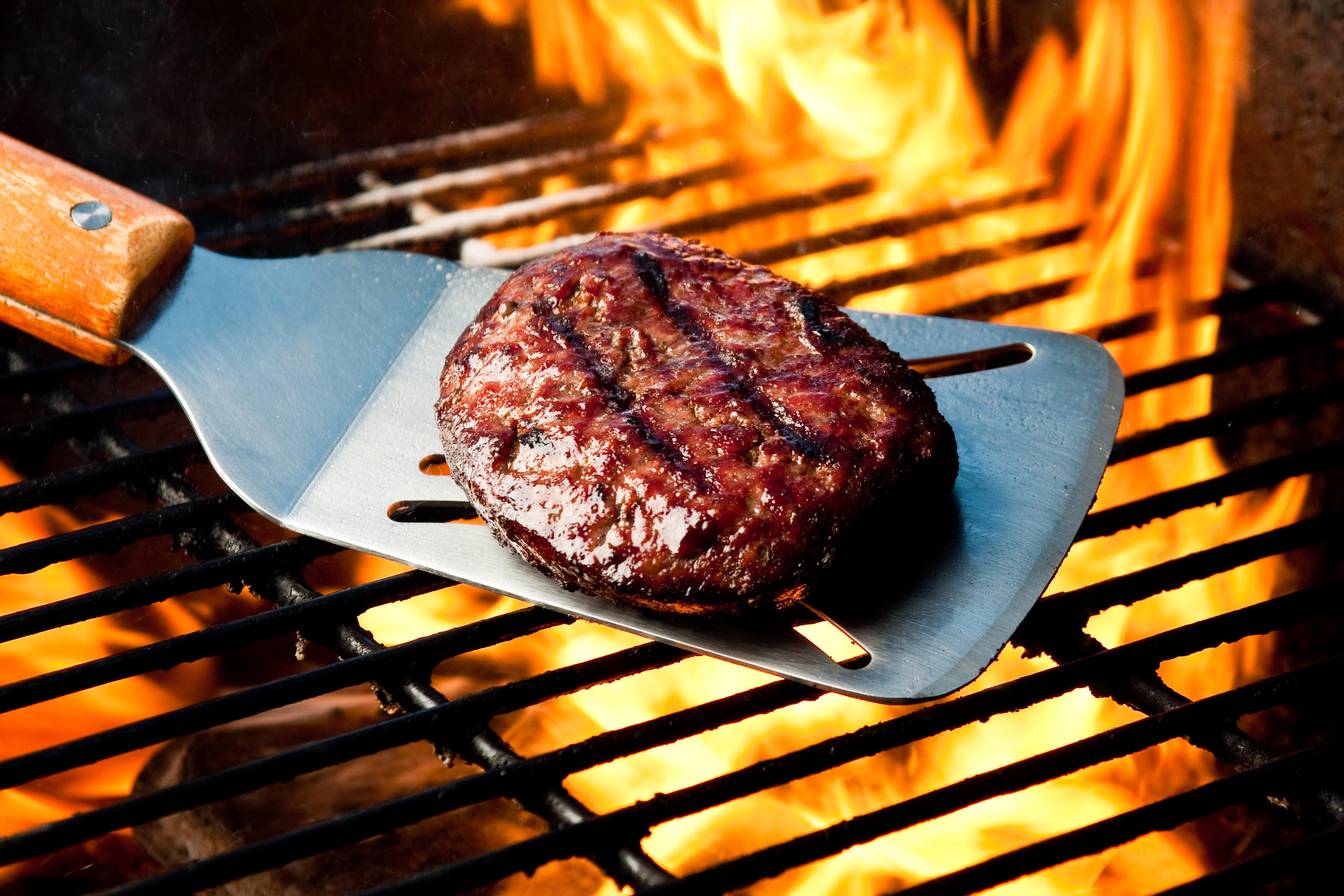 Una hamburguesa braseada en una espátula sobre una llama.