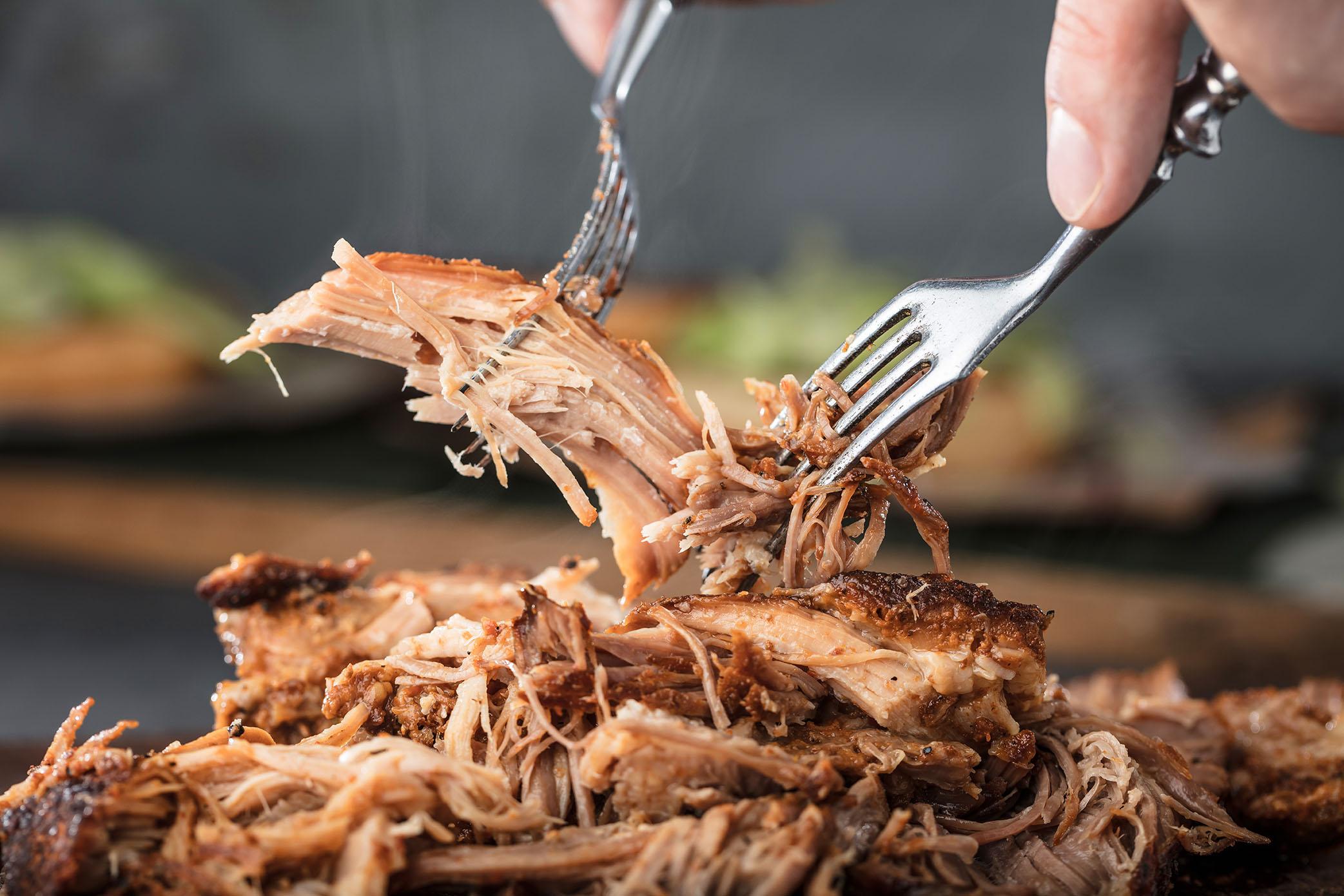 Un tenedor con cerdo asado lentamente sobre una bandeja de cerdo