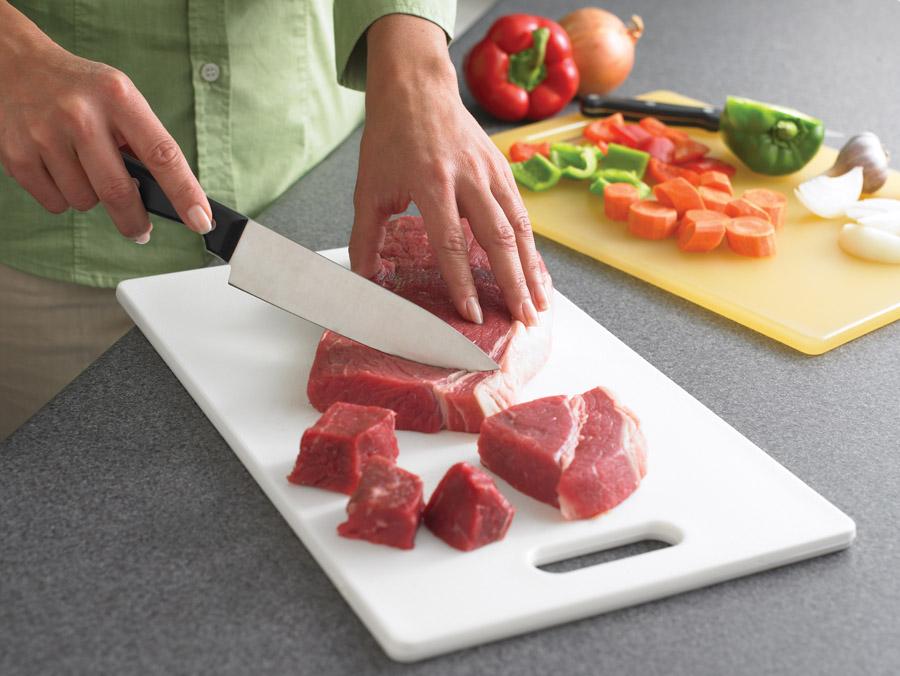 Una persona cortando carne cruda sobre una tabla de cortar. En otra tabla de cortar se ven zanahorias, pimientos y cebollas picados.