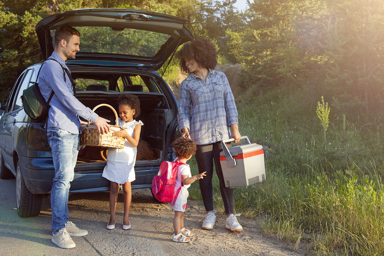 Una familia con dos niños pequeños sacando neveras y bocadillos del maletero del auto.