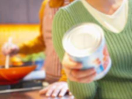 Woman inspecting canned food in kitchen