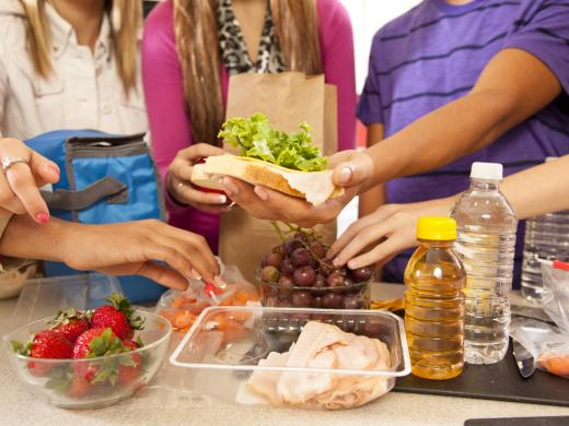 A group of young people gather around a counter where they are preparing healthy packed lunch together, including a turkey sandwich, baby carrots, strawberries, and graps.