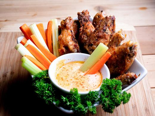 A dish with celery, carrot sticks, and chicken wings and  a bowl of buffalo sauce.