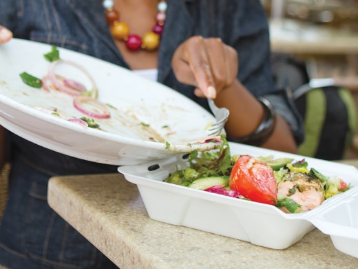 A person is using a fork to move food from a platter into a to-go container.
