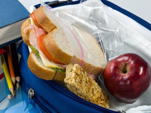Un almuerzo para llevar con un sándwich, una barra de granola y una manzana.