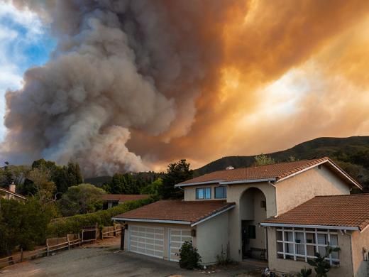Incendio detrás de una casa.